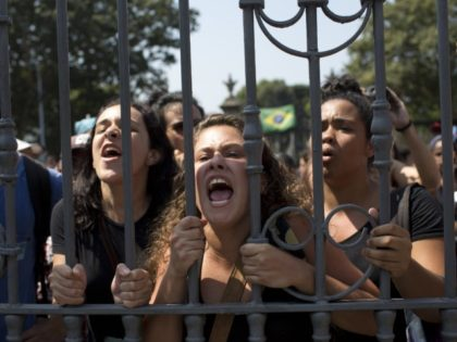 Students and National Museum employees protest outside the institution after it was gutted by an overnight fire in Rio de Janeiro, Brazil, Monday, Sept. 3, 2018. Recriminations flew over who was responsible for the loss of at least part of Latin America's largest archive of historical artifacts, objects and documents. …