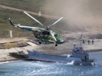 "A Russian navy landing vessel unloads an armored vehicle as a military helicopter flies overhead during Russian military maneuvers Vostok 2018 on the training ground ""Klerk"", about 50 kilometers (31 miles) south of Vladivostok, Russian Far East port, Russia, Saturday, Sept. 15, 2018. The weeklong Vostok 2018 maneuvers are the …"