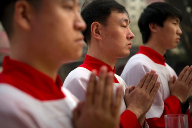 "In this Saturday, March 31, 2018, file photo, Chinese acolytes pray during a Holy Saturday Mass on the evening before Easter at the Cathedral of the Immaculate Conception, a government-sanctioned Catholic church in Beijing. On Saturday, Sept. 22, 2018, the Vatican announced it had signed a ""provisional agreement"" with China …"