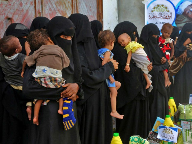 Yemeni women and children wait during food distribution in the province of Hodeida on May 30, 2018. - Hodeida port, Yemen's largest entry point for aid, is now in the crosshairs of the Saudi-led coalition which is intent on cutting off the Huthi rebels from alleged Iranian arms shipments. The …