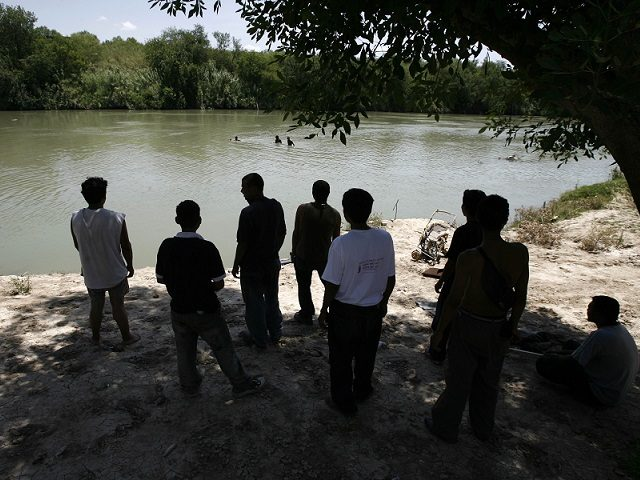 After thirty days crossing Mexico, a group of Honduran migrants watch from the Mexican side of the Rio Grande as others take a bath while waiting for a good moment to cross the river into the U.S. in the border city of Nuevo Laredo, Mexico on Thursday, May 25, 2006. …