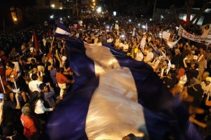 Hundreds of demonstrators with a Honduran flag protest in favor of the caravan of migrants who are currently stuck on the Guatemala-Mexico border, in front of the American embassy, in Tegucigalpa, Honduras, Friday, Oct. 19, 2018. A U.S.-bound caravan that once totaled more than 3,000 Central American migrants looked to …