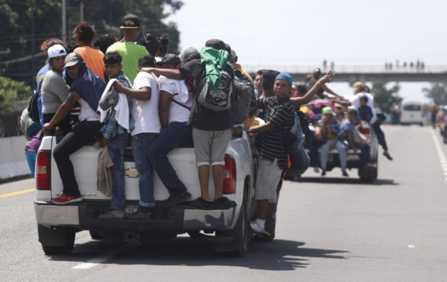 Central American migrants making their way to the U.S. in a large caravan cling to the trucks of drivers who offered them free rides, as they arrive to Tapachula, Mexico, Sunday, Oct. 21, 2018. Despite Mexican efforts to stop them at the Guatemala-Mexico border, about 5,000 Central American migrants resumed …