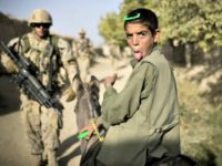 A boy on a donkey reacts as Canadian soldiers with the 1st RCR Battle Group, The Royal Canadian Regiment, patrol in Salavat, southwest of Kandahar, on September 11, 2010. Minutes later the soldiers were attacked by grenades while leaving the village.