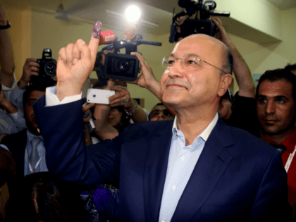 Barham Salih (R), a senior PUK politician who has held multiple top positions including prime minister of the Kurdish region shows his ink-stained finger after voting in the Kurdistan's legislative election at a polling station on September 21, 2013 in the northern Kurdish city of Sulaimaniyah. Iraq's Kurds vote for …
