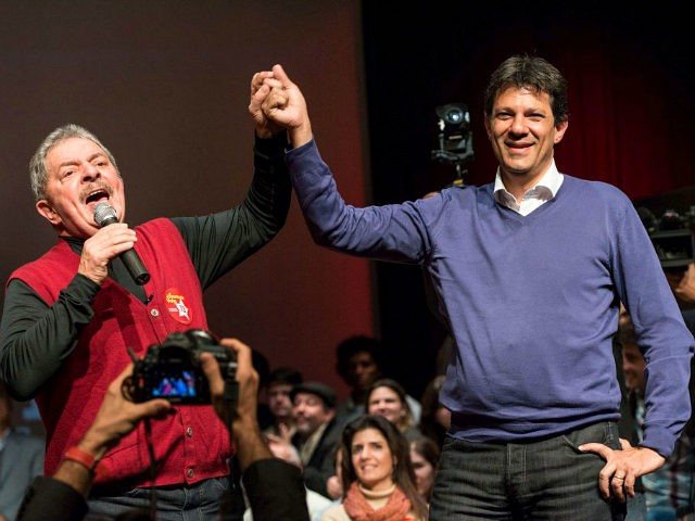 Brazilian former president Luiz Inacio Lula da Silva (L) raises the hand of the mayoral candidate of the Workers Party (PT) Fernando Haddad during a campaign rally in Sao Paulo, Brazil, on September 27, 2012. The Sao Paulo mayoral race pits an ex-television consumer advocate against candidates of Brazil's two …