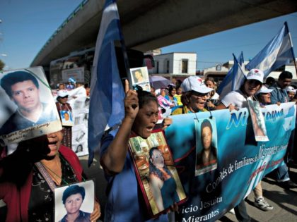 Members of a caravan of Central American mothers hold photographs of their disappeared children as they walk from their vehicles to the railroad tracks near what was once a migrant shelter in Lecheria on the outskirts of Mexico City, Friday, Oct. 26, 2012. The convoy, mostly comprised of women from …