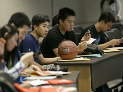 In this photo made Saturday, Aug. 22, 2015, Weikang Nie, a finance graduate student from China, sits which his basketball and fellow Chinese students during a new student orientation at the University of Texas at Dallas in Richardson, Texas. The U.S. Census Bureau research shows immigrants from China and India, …