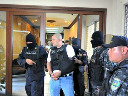 Alleged drug trafficker Mario Ponce Rodriguez (C) --whose extradition has been requested by the US-- is taken under custody to a hearing in court in Tegucigalpa on October 10, 2011.