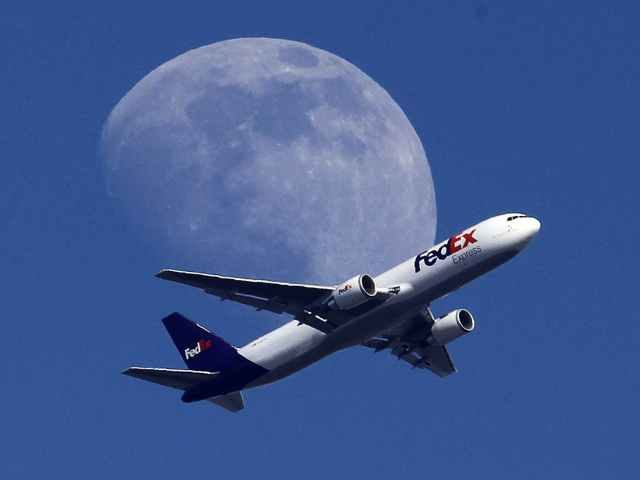 Fedex Plane flying in front of moon