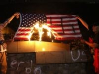 Protesters in Support of Caravan Paint Swastika on U.S. Flag, Burn It