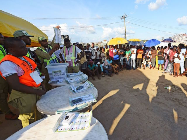 A picture taken on September 22, 2018 shows people watching as an electoral officer raises a ballot to count results in a ward after the Osun State gubernatorial election in Ede, near Osogbo, Osun State in southwest Nigeria. - The Osun election is seen as a litmus test for the …