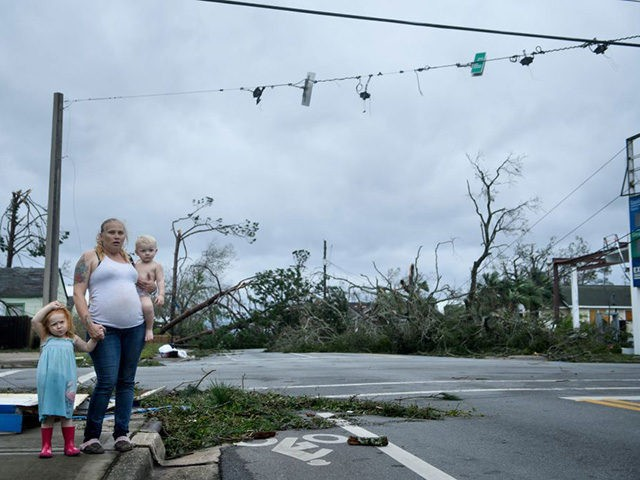 TOPSHOT - A woman and her children wain near a destroyed gas station after Hurricane Michael in Panama City, Florida on October 10, 2018. - Michael slammed into the Florida coast on October 10 as the most powerful storm to hit the southern US state in more than a century …