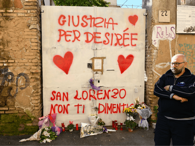 A resident stands by the entrance of a sequestered derelict building in the San Lorenzo district of Rome on October 24, 2018, a week after a female teenager was found dead in the building. - Italy's Interior minister Matteo Salvini paid a visit to the neighborhood on October 24, a …