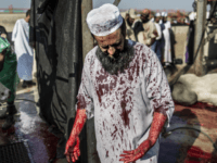 A South African Muslim, his jalabiya stained with blood from a bull, stands with others as they gathered during a ritual slaughter at a halal abattoir in Lenasia, 30km south of Johannesburg, for Eid al-Adha on September 24, 2015. The world's 1.5 billion Muslims is marking Eid al-Adha, the Feast …