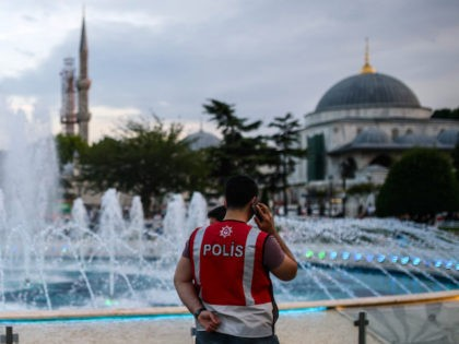 A Turkish police officer speaks on the phone as he stands guard by a fountain on June 6, 2016 at the Blue mosque square in Istanbul, during the first day of the holy month of Ramadan. More than a billion Muslims observed the start of Ramadan on May 6 but …