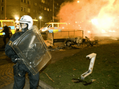 A riot police officer stands guard while colleagues extinguish burning barricades on the main road in the heavily-immigrant populated neighborhood of Rosengaard of the southern Swedish city of Malmoe on December 19, 2008. Some 100 youths rioted in late December 18 for the second straight night, setting cars and garbage …