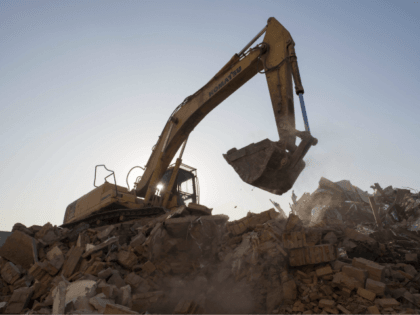In this picture taken on December 8, 2017, a bulldozer clears debris from buildings demolished by authorities in a migrant housing area on the outskirts of Beijing. The hundreds of millions of migrants who moved from the countryside to the cities may have fuelled China's dramatic economic boom of recent …