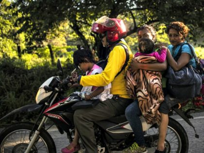 A Honduran migrant family heading in a caravan to the US, travels on a motorbike near Mapastepec, southern Mexico on October 25, 2018. - Thousands of Central American migrants crossing Mexico toward the United States in a caravan have resumed their long trek, walking about 12 hours to their next …
