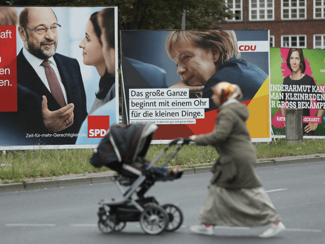 BERLIN, GERMANY - SEPTEMBER 08: A Muslim woman pushes a pram past election campaign billboards that show German Social Democrat (SPD) chancellor candidate Martin Schulz (L), German Chancellor and Christian Democrat (CDU) Angela Merkel (C) and Greens Party co-lead candidate Katrin Goering-Eckardt on September 8, 2017 in Berlin, Germany. Germany …