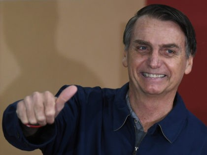Brazil's right-wing presidential candidate for the Social Liberal Party (PSL) Jair Bolsonaro gives his thumb up after casting his vote during the general elections, in Rio de Janeiro, Brazil, on October 7, 2018. - Polling stations opened in Brazil on Sunday for the most divisive presidential election in the country …