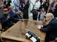 Rapper Kanye West, left, speaks during a meeting with U.S. President Donald Trump as NHL Hall of Famer Jim Brown looks on in the Oval office of the White House on October 11, 2018 in Washington, DC. (Photo by Oliver Contreras - Pool/Getty Images)
