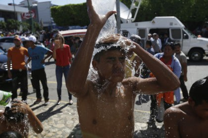 Central American migrants making their way to the U.S. in a large caravan bathe using water from a fire hydrant at the main plaza in Tapachula, Mexico, Monday, Oct. 22, 2018. Thousands of Central American migrants hoping to reach the U.S. were deciding Monday whether to rest in this southern …
