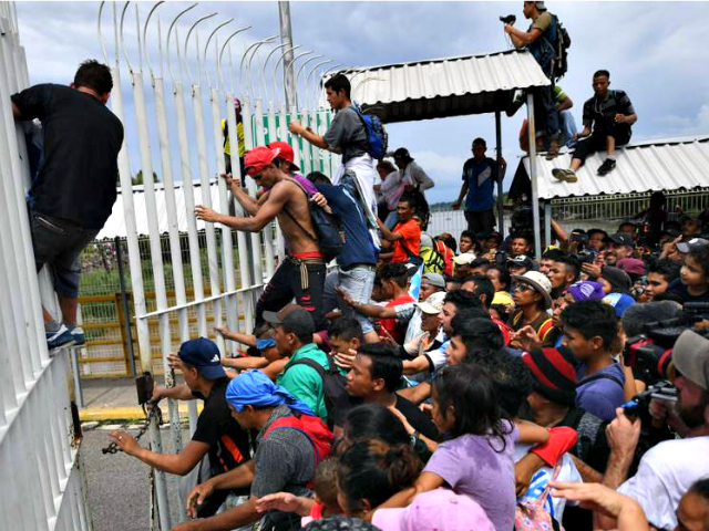 Migrants Break Through Border Fence