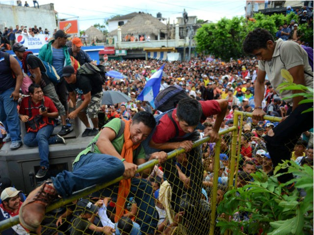 Thousands of Honduran migrants gather at a fence as some climb towards Mexico in Tecun Uman, Guatemala, Friday, Oct. 19, 2018. Migrants broke down the gates at the border crossing and began streaming toward a bridge into Mexico. After arriving at the tall, yellow metal fence some clambered atop it …