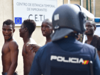 CEUTA, SPAIN - AUGUST 22: African migrants enter the Centre for Temporary Stay of Immigrants (CETI) after successfully breaching the border from Morocco into the Spanish exclave of Ceuta on August 22, 2018 in Ceuta, Spain. This morning 100-150 mostly sub-saharan refugees crossed the barb wire fence from Morocco into …