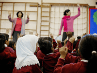 LONDON, UNITED KINGDOM: WITH 'RELIGIOUS EDUCATION A FESTIVAL OF LIGHT IN BRITAIN' A young girl wearing a muslim headscarf listens as two teachers instruct the class in singing christmas songs at Featherstone Primary school 09 December 2003 in Southall London. Sitting cross-legged the children intone a Sikh chant accompanied by …