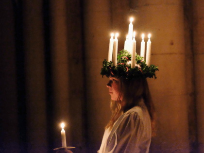 YORK, ENGLAND - DECEMBER 09: Matilda Jarl, 15, from the Jarfalla chamber choir near Stockholm, Sweden plays the role of Lucia as she leads the procession during the Swedish Sankta Lucia Festival of Light service at York Minster on December 9, 2016 in York, United Kingdom. The Sankta Lucia service …