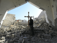 TOPSHOT - A member of the Syrian Arab-Kurdish forces places a cross in the rubble ahead of a Christmas celebration at the heavily-damaged Armenian Catholic Church of the Martyrs in the city centre of the eastern Syrian city of Raqa on December 26, 2017 following a mine clarence operation at …