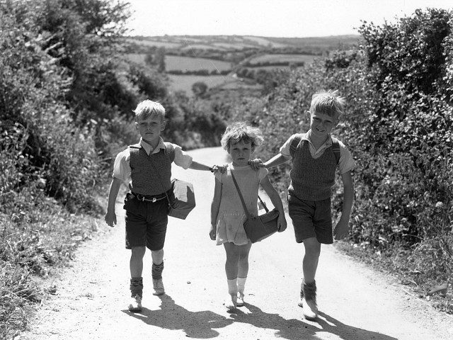 Evacuee children from London, on their way to school in Devon, World War II 1940. The children are (left to right) Ronald (7), Iris (4) and David Blackie (8), of Campbell Buildings in Lower Marsh, near Waterloo Station, London. They are staying in a farmhouse with a Mrs Shillabeer. (Photo …