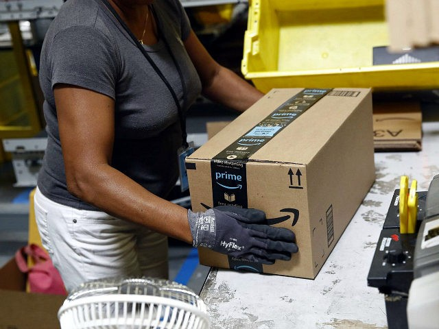FILE- In this Aug. 3, 2017, file photo, Myrtice Harris applies tape to a package before shipment at an Amazon fulfillment center in Baltimore. Amazon is boosting its minimum wage for all U.S. workers to $15 per hour starting next month. The company said Tuesday, Oct. 2, 2018, that the …