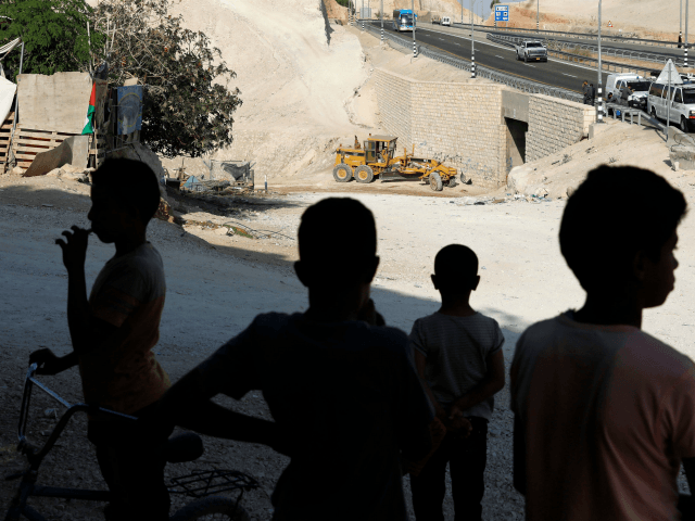 Bedouin children look at an Israeli army excavator in the Palestinian Bedouin village of Khan al-Ahmar, east of Jerusalem in the occupied West Bank on October 16, 2018. - Israel plans to demolish the Bedouin community, which it says was built illegally, despite international calls for a reprieve. (Photo by …