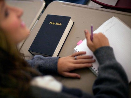 In this Thursday, Oct. 20, 2011, photo, a bible sits on the desk of Bradley Sabin, a junior, as she takes notes during Bible class at Woodland High School in Cartersville, Ga. Georgia was the first state in the country to allow Bible classes in public schools, but the number …