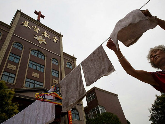 In this photo taken Saturday, June 2, 2018, a woman hangs laundry near a church in the city of Pingdingshan in central China's Henan province. Under President Xi Jinping, China's most powerful leader since Mao Zedong, believers are seeing their freedoms shrink dramatically even as the country undergoes a religious …