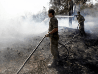 Israeli soldiers attempt to extinguish a fire in a forest field near the Kibbutz of Nahal Oz, along the border with the Gaza Strip, on July 17 after it was caused by inflammable material attached to a balloon flown by Palestinian protesters from across the border. (Photo by MENAHEM KAHANA …