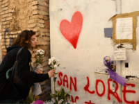 A young woman places flowers at the entrance of a sequestered derelict building in the San Lorenzo district of Rome on October 24, 2018, a week after a female teenager was found dead in the building. - The body of sixteen-year-old Desiree Mariottini was found dead overnight on October 19 …