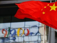 The Google logo is reflected in windows of the company's China head office as the Chinese national flag flies in the wind in Beijing on March 23, 2010 after the US web giant said it would no longer filter results and was redirecting mainland Chinese users to an uncensored site …