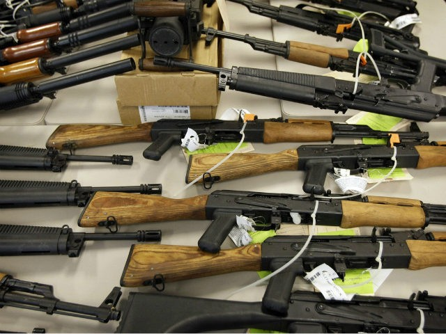 In this Jan. 25, 2011, file photo, a cache of seized weapons that were to be smuggled into Mexico is displayed in Phoenix. Among the thousands of immigrants who have been coming across the U.S.-Mexico border in recent months, many are seeking to escape gang and drug violence raging in …