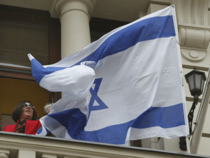 Israeli Ambassador Anna Azari holds the Israeli flag from a balcony of the historic Bristol Hotel in Warsaw, Poland, during a ceremony on Tuesday, Oct. 23, 2018. The flag hanging was a re-enactment ceremony marking the 70th anniversary of Israel's first diplomatic outpost as a new nation at the same …