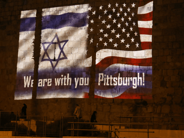 People walk under the US and the Israeli flags projected on the walls of Jerusalem old city on October 28, 2018, organised by Jerusalem municipality to show solidarity with the Pittsburgh Jewish community following the shooting attack at the Tree of Life synagogue in Pittsburgh, Pennsylvania. (Photo by Menahem KAHANA …