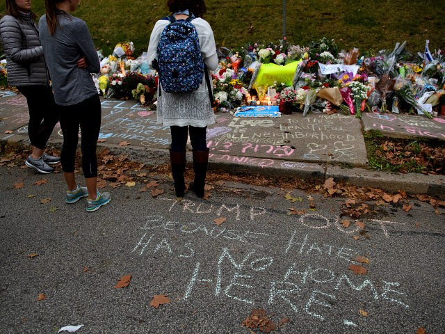 PITTSBURGH, PA - OCTOBER 29: People pause in front of at a memorial for victims of the mass shooting that killed 11 people and wounded 6 at the Tree Of Life Synagogue on October 29, 2018 in Pittsburgh, Pennsylvania. President Donald Trump will be visiting the synagogue Tuesday to pay …