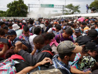 Mexican Federal Police spray tear gas during clashes with thousands of Central American migrants, at the border crossing in Ciudad Hidalgo, Mexico, Friday, Oct. 19, 2018. Central Americans traveling in a mass caravan broke through a Guatemalan border fence and streamed by the thousands toward Mexican territory, defying Mexican authorities' …