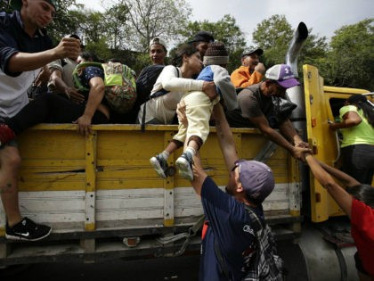 Honduran migrants bound to the U.S border climb into the bed of a truck in Zacapa, Guatemala, Wednesday, Oct. 17, 2018. The group of some 2,000 Honduran migrants hit the road in Guatemala again Wednesday, hoping to reach the United States despite President Donald Trump's threat to cut off aid …