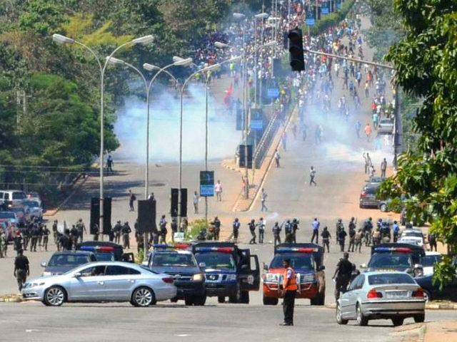 Nigerian police officers fire teargas at supporters of Islamic Movement of Nigeria (IMN) as they protest against the imprisonment of their leader Ibrahim Zakzaky, in Abuja, on October 30, 2018. - Nigerian police fired shots and tear gas at thousands of supporters of an imprisoned Shiite cleric in Abuja on …