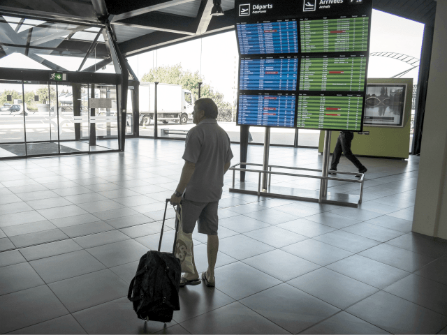 A passengers walk through a hall past timetables displaying cancelled flights at the Lyon-Saint-Exupery airport on September 15, 2014. French flag carrier Air France said it would be forced to scrap half its flights on September 15 as pilots strike in protest at the company's plan to develop its low-cost …