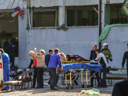 TOPSHOT - EDITORS NOTE: Graphic content / Rescuers carry an injured victim of a blast at at a college in the city of Kerch on October 17, 2018. - Thirteen people were killed and 50 more wounded, most of them teenagers, after a blast tore into a college canteen in …